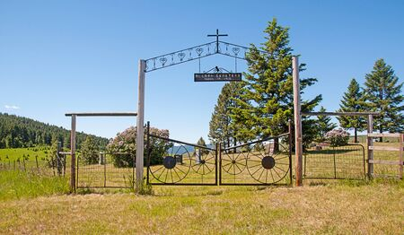 Molson cemetery sign with a cross and iron gate with wagon wheels.  Found in Molson, Washington this decorative gate encloses the graveyard.