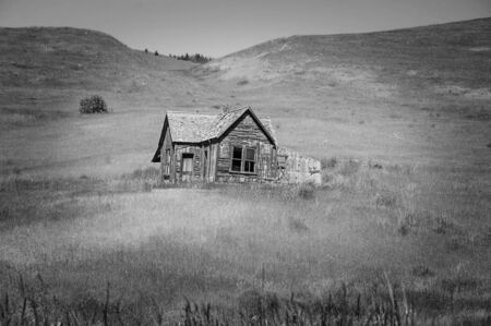 Black and white pioneer homestead. An old pioneer home with broken windows and abandoned piece of history. Rolling hills landscape with a vignette edge. Found in Eastern Washington.