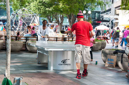 Seattle, WA USA August 23, 2014:  Men enjoy the table tennis or ping pong game in Occidental park in Pioneer Square in this urban city image in Seattle.