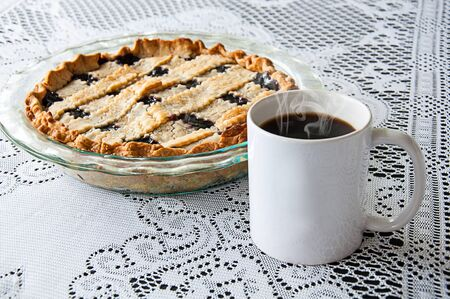 White coffee mug and blueberry pie still life on a lace tablecloth. Styled product photo with copy space on the coffee cup for custom text or graphics. Steaming hot black coffee and pie dessert with lattice crust. Traditional food and drink for mockups.