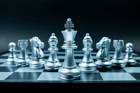 Row of silver chess team on board , black background