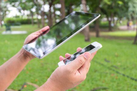 man hand holding tablet or smart phone , garden background