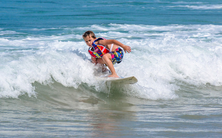 PHUKET, THAILAND - SEPTEMBER 21: A little Western boy practicing sufing in Kata beach -Phuket island, Thailand on September 21,2014. Kata beach is the paradise for surfer on Monsoon season. Editorial