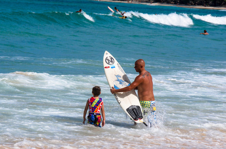 PHUKET, THAILAND - SEPTEMBER 21: Father teaching his little son how to sufing in Kata beach - Phuket island, Thailand on September 21,2014. Sajtókép