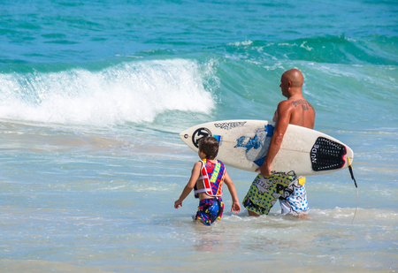 PHUKET, THAILAND - SEPTEMBER 21: Father teaching his little son how to sufing in Kata beach - Phuket island, Thailand on September 21,2014. Editorial