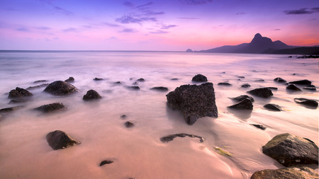 Romantic atmosphere in peaceful Sunset at Bai nhat beach Condao island-Vietnam. Taking with long exposure in the evening smooth wavy motion by Big rocks near shoreline, pink horizon with sun rays.