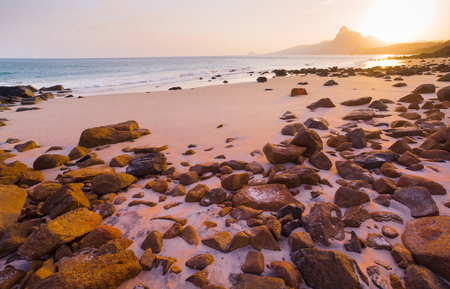 Romantic atmosphere in peaceful Sunset at Bai nhat beach Condao island-Vietnam. Taking with long exposure in the evening smooth wavy motion by Big rocks near shoreline, pink horizon with sun rays. Imagens - 79799992
