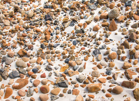 Close-up of smooth round pebble stones on the sand beach backgound