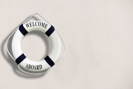 White color Life buoyancy with welcome aboard on it hanging on white concrete wall.had space on right side for your text.