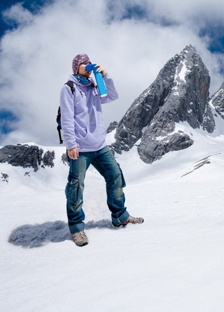 Climber breathing with mini portable oxygen cylinger to avoid and treat Altitude Sickness synptom Imagens - 80172533