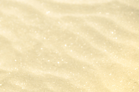 Golden glitter on blurry sand background Imagens - 81429960