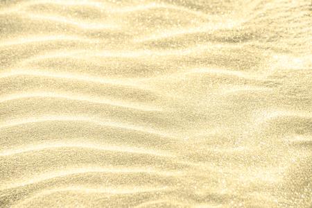 Golden glitter on sand background