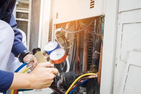 locales comerciales: Técnico está comprobando aparato de aire acondicionado