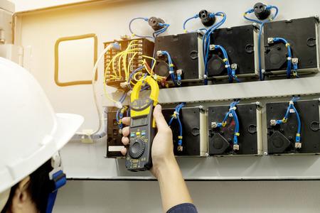 기술자는 클램프 미터로 전압 또는 전류를 측정하고 있습니다.