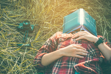 man lying down: hipster man lying down on grassland napping tired after reading book with nature around outside Stock Photo