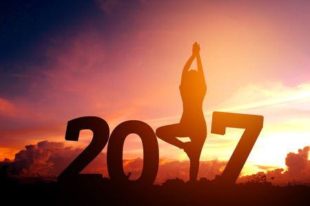 new years resolutions: Silhouette young woman practicing yoga on 2017 new year Stock Photo
