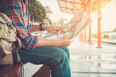젊은 남자 여행자가지도와 함께 앉아 기차, 빈티지 톤을 기다리는 여행을 선택하십시오 스톡 콘텐츠