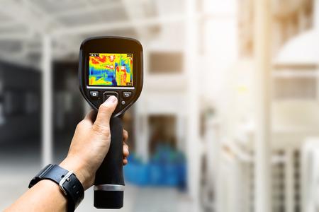 기술자가 열 화상 카메라를 사용하여 공장에서 온도를 확인합니다. 스톡 콘텐츠