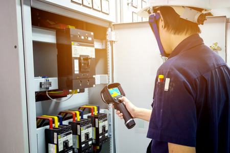 기술자는 열 화상 카메라를 사용하여 공장에서 온도를 확인합니다.