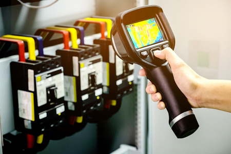 technician use thermal imaging camera to check temperature in factory Imagens