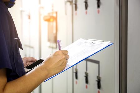 기술자가 발전소의 제어판에 데이터 전압 또는 전류를 기록하고 있습니다.