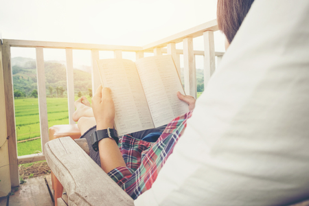 hassock: Young man reading a book lying in relaxing bed at terrace with green nature view