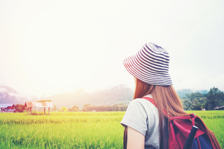 Traveling woman with backpack at sunny day.