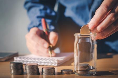 저축 돈 개념 남자 손 퍼 팅 행 및 동전 쓰기 금융 스톡 콘텐츠