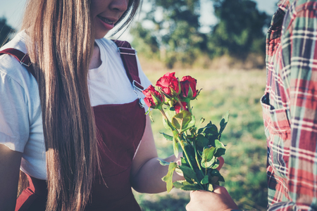 loving couple - man with rose waiting his woman in park