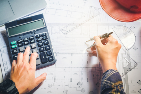 architect: Architect or engineer working in office on blueprint. Architects workplace , blueprints, ruler, helmet and divider. Construction concept. Engineering tools