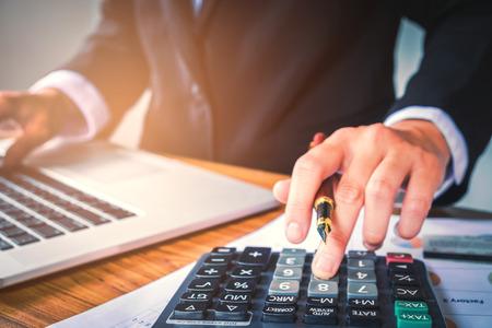 Le mani dell'uomo d'affari con il calcolatore all'ufficio e ai dati finanziari che analizzano contando sullo scrittorio di legno Archivio Fotografico - 78977514