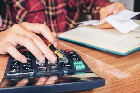 사업가 손을 계산기 및 사무실 및 재무 데이터 나무 책상에 계산 분석 비용 스톡 콘텐츠