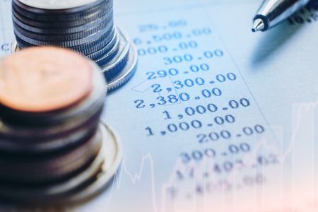 financial analyzing concept Pen and coin and on paper report. Stockfoto