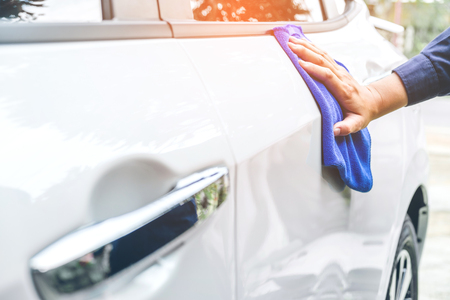 man cleaning car with microfiber cloth white car
