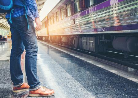 Traveler man  waits train on railway platform Stockfoto