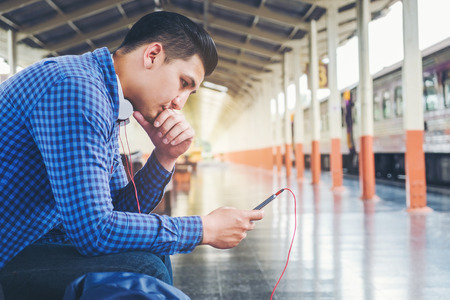 Traveler Man using tablet and phone waiting for train on the station Stock Photo