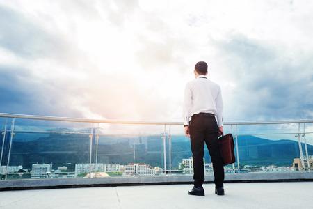 Empresario de pie en un techo y mirando a la ciudad Concepto de éxito y pensamiento Foto de archivo - 82962871