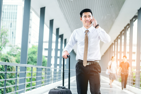 adentro y afuera: Professional businessman Travel using smartphone talking on his phone smiling happy outside walking inside in airport