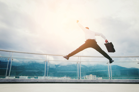 Businessman Jump on a roof and looking at city Success  concept