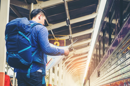 Tourist backpacker using map to travel at train station