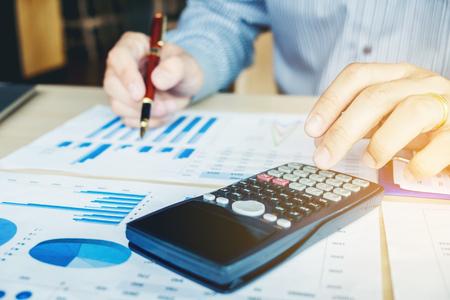 Le mani dell'uomo d'affari con il calcolatore all'ufficio e ai dati finanziari che analizzano conteggio Archivio Fotografico - 85252644