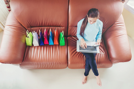 Woman with laptop shopping online with debit card on sofa in home