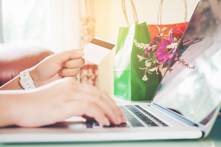 Closeup credit card ,Woman shopping online using laptop with credit card enjoying in home Stock Photo