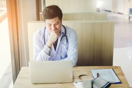 Doctor is working in office sitting, thinking about Disease problem of patient