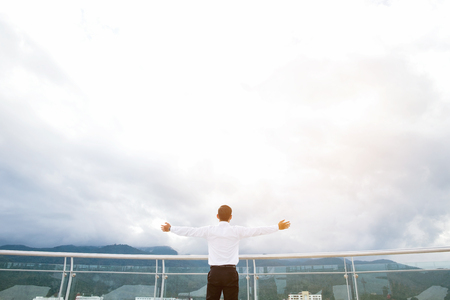 Businessman standing keeping arms raised on a roof and looking at city Success  concept Stock Photo