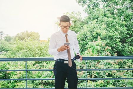 Businessman Using Mobile Phone Hand holding Coffee cup outdoor