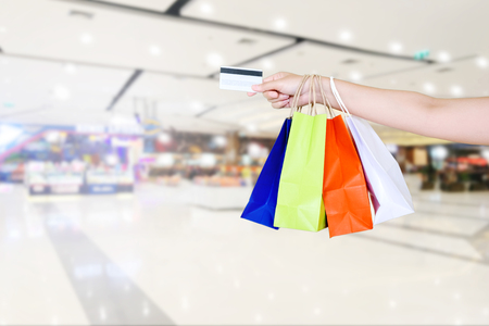 Woman holding shopping bag and Credit card in Shopping mall Stock Photo