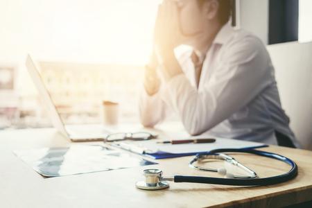 Stethoskop und Doktor, die mit Laptopstresskopfschmerzen über Arbeit im Krankenhaus sitzen Standard-Bild