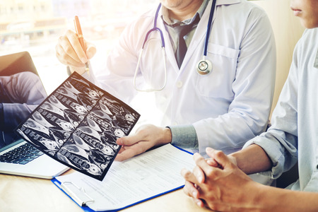 Doctor consulting with patient presenting results on x-ray film About the problem of the patient Stockfoto