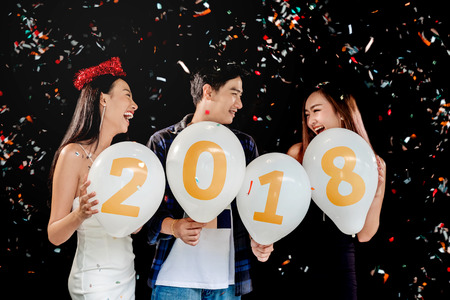 Newyear party ,celebration party group of asian young people holding balloon numbers 2018 happy and funny concept